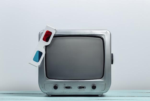 Retro odbiornik telewizyjny z anaglyfowymi okularami 3d na białej ścianie white