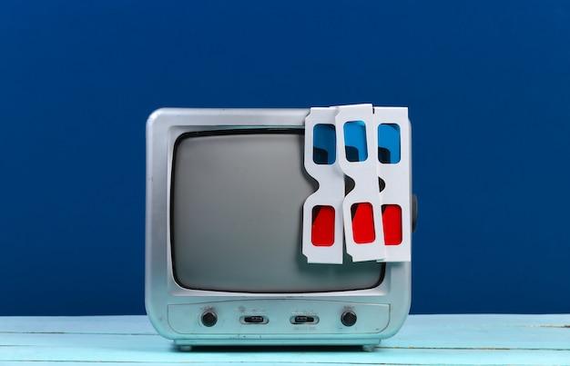Retro odbiornik telewizyjny z anaglyfowymi okularami 3d na klasycznym niebieskim