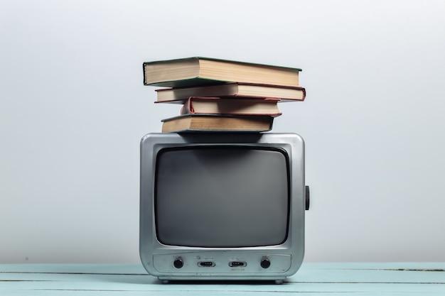 Retro odbiornik telewizyjny ze stosem książek na białym tle