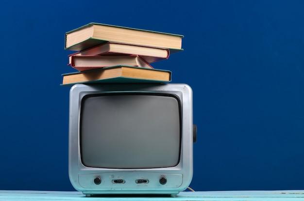Retro odbiornik telewizyjny ze stosem książek na klasycznym niebieskim kolorze