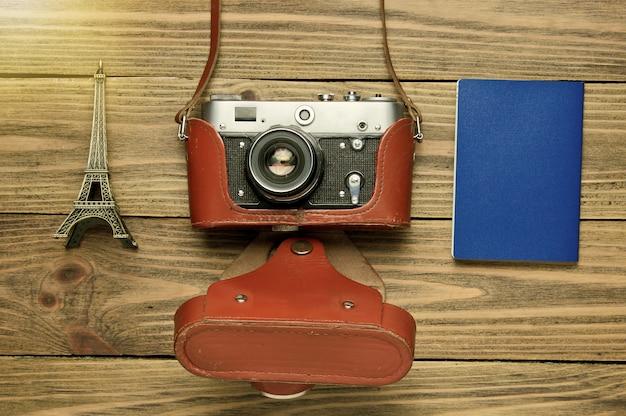 Retro płaski obraz z retro aparatem, statuetkę wieży eiffla i paszport na drewnianym tle, widok z góry. stary aparat filmowy mody. podróż do paryża