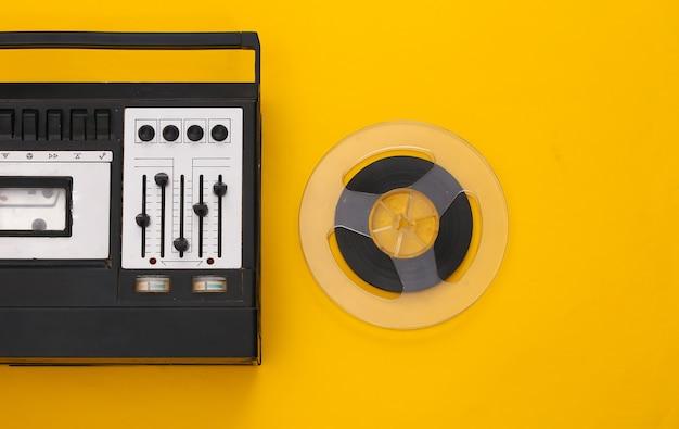 Retro płaskie świeckich. retro magnetofon stereo i magnetyczna szpula audio na żółto
