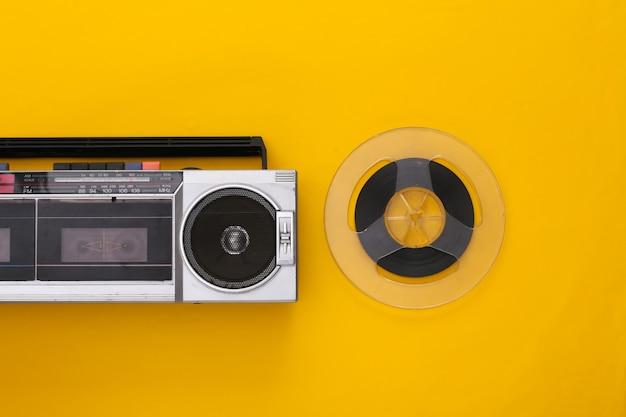 Retro płaskie świeckich. retro przenośny stereofoniczny magnetofon kasetowy i magnetyczna szpula audio na żółtym tle