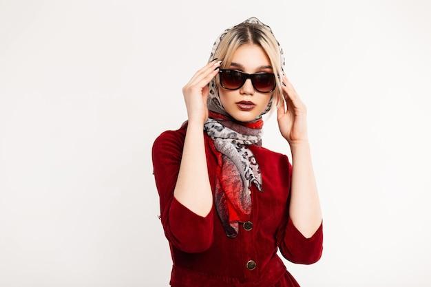 Retro portret seksowna młoda kobieta z pięknymi ustami w modny szalik lampart na głowie w stylowych okularach przeciwsłonecznych w czerwonej eleganckiej sukience. wspaniała dziewczyna moda model stoi i prostuje okulary
