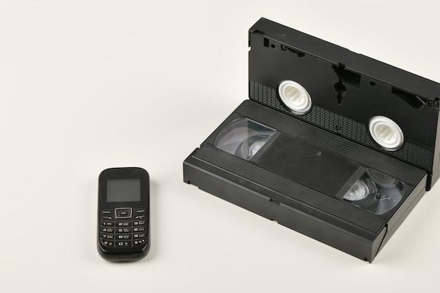 Retro przedmioty na białym tle. telefon z przyciskiem i kaseta wideo. technologia mediów analogowych z przeszłości. skopiuj miejsce