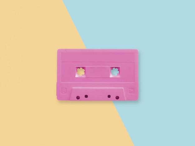 Retro różowa kaseta magnetofonowa na pastelowej powierzchni duotone