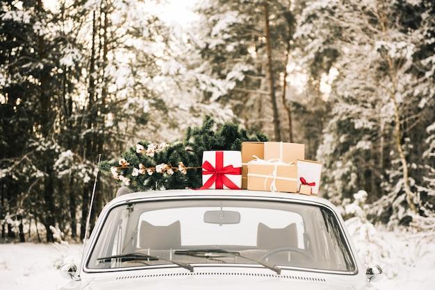 Retro samochód z prezentami i choinką w śnieżnym lesie zimą