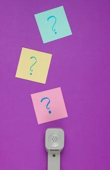 Retro słuchawki i znaki zapytania na kartkach papieru