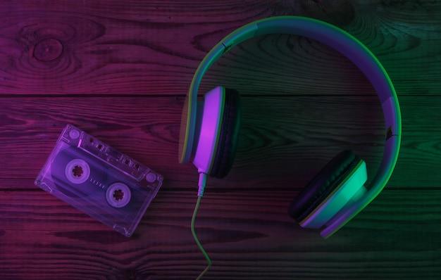 Retro słuchawki stereo z kasetą audio. neonowe fioletowe i zielone światło