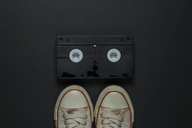 Retro stare trampki i kaseta wideo na czarnym tle. 80s. widok z góry