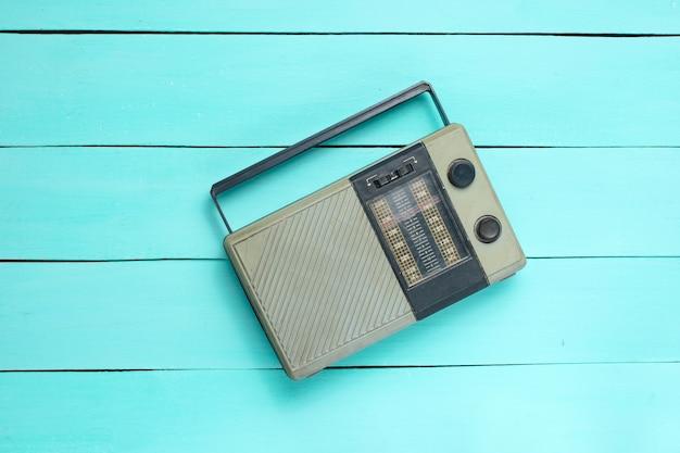 Retro stary odbiornik radiowy na niebieskim tle drewnianych. widok z góry. przestarzała technologia