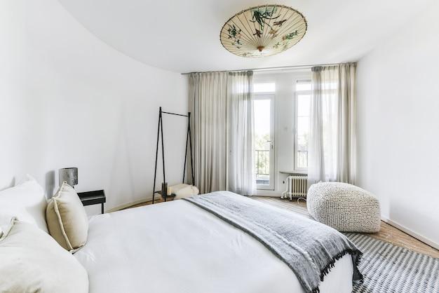 Retro stolik nocny z lampką przy wygodnym łóżku pod oknem w nowoczesnej sypialni