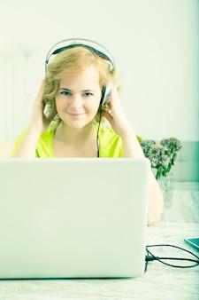 Retro stylizowany wizerunek kobiety słuchającej muzyki przed laptopem