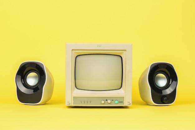 Retro szary monitor z głośnikami na żółtym tle. stylowy sprzęt vintage.