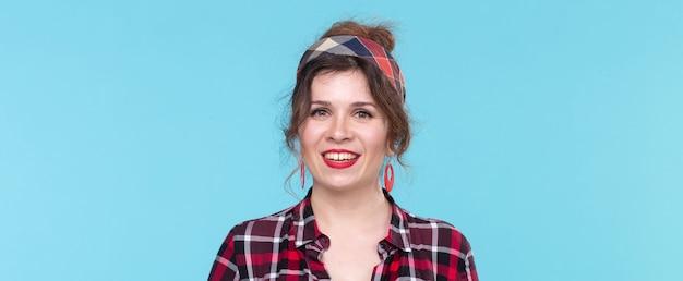 Retro, vintage, koncepcja ludzi - kobieta w stylu retro uśmiechnięta na niebieskim tle z kopią przestrzeni