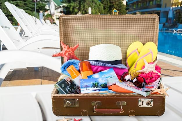 Retro walizka z przedmiotami podróżnymi na biurku