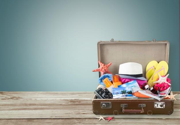 Retro walizka z przedmiotami podróżnymi na tle