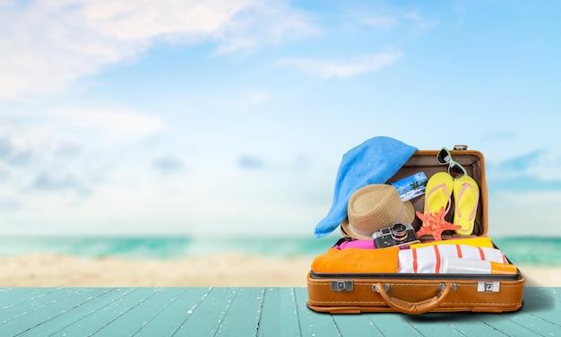 Retro walizka z przedmiotami podróży na tle morza