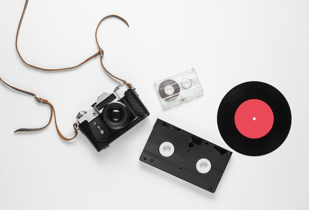Retro widok z góry martwa natura. płyta winylowa, zabytkowa kamera filmowa, kaseta wideo i audio na białym tle. leżał na płasko