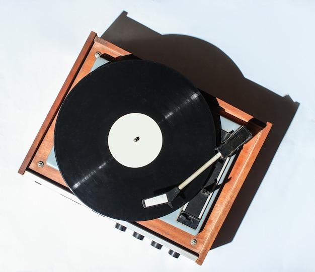 Retro winylowy gramofon na białym tle. zdjęcie z cieniami, twarde światło, widok z góry