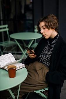 Retro wyglądająca osoba niebinarna sprawdzająca telefon
