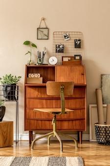 Retro wystrój sali warsztatowej z drewnianym biurkiem i krzesłem w stylu vintage, kostką, roślinami, kaktusami, książkami, zdjęciami i eleganckimi akcesoriami osobistymi. stylowy wystrój domu w stylu vintage. ściana beżowa.