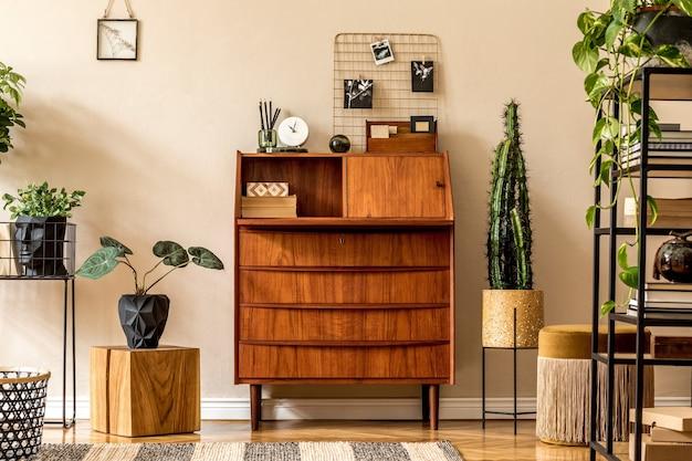Retro wystrój salonu z drewnianym biurkiem vintage, półką, złotą pufą, kostką, roślinami, kaktusami, książkami.