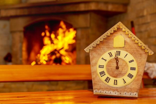 Retro zegar z kukułką z cyframi rzymskimi na tle kominka z ogniem. na tarczy 12 godzin bez 5 minut.