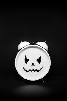 Retro zegar z przerażającą twarzą na ciemnym tle. koncepcja czasu halloween lub strachu. skopiuj miejsce