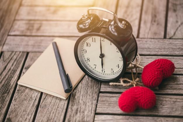 Retro zegarowy czas przy 6 godziną z notatnikiem lub notatką na drewno stole