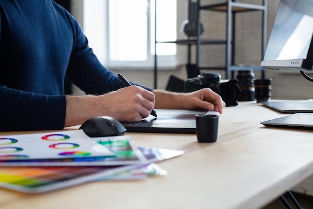 Retusz zdjęć w specjalnym programie. portret grafika pracującego w biurze z laptopem, monitorem, tabletem do rysowania graficznego i paletą kolorów. miejsce pracy retuszera w studiu fotograficznym. agencja kreatywna.
