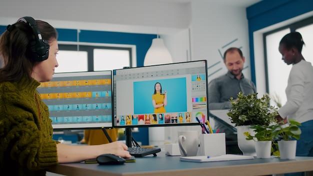 Retuszer zakładający zestaw słuchawkowy pracujący nad rysowaniem projektu ołówkiem z rysikiem