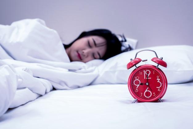 Rewolucjonistka zegar z pięknym kobiety dosypianiem na łóżku