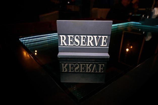 Rezerwat z drewnianego znaku stoi na czarnym stole ze szkła