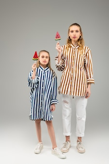 Rezolutne jasnowłose siostry, które mają podobne stroje, stojąc z cukierkami na drewnianym patyku