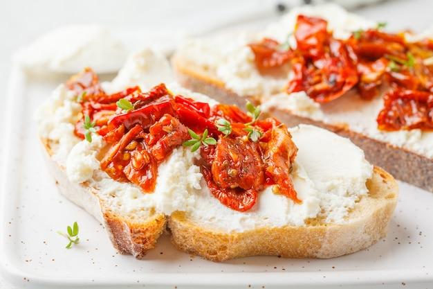 Ricotta i słońce suszone pomidory kanapki na białej tablicy.