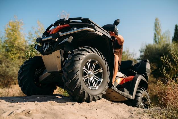 Rider atv wspinający się na górę piasku w kamieniołomie. mężczyzna kierowca w kasku na quadzie w piaskownicy