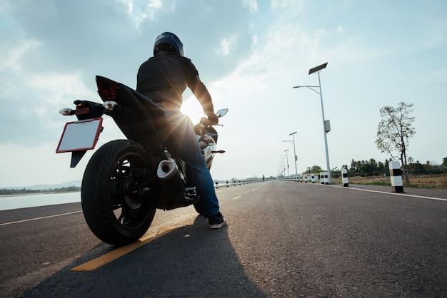 Rider motocykl na drodze. dobrze się bawiąc jeżdżąc pustą drogą