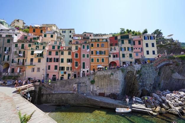 Riomaggiore, włochy - 20 lipca 2021: kolorowe domy zwisające klify w parku narodowym cinque terre, liguria, włochy