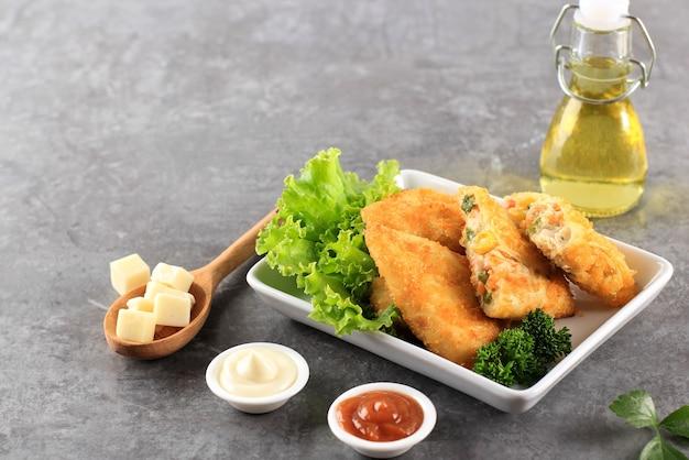 Risole warzywne w kształcie trójkąta. cienkie naleśniki nadziewane kukurydzą rogusa, marchewką i zieloną fasolą, podawane na białym talerzu z serem, majonezem i sosem chili. kopiuj przestrzeń na szarym tle