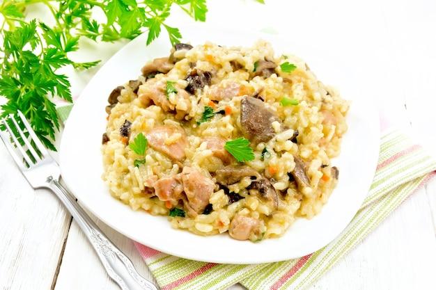 Risotto ryżowe z pieczarkami, mięsem z kurczaka, serem i czosnkiem w talerzu na ręczniku, widelcu i pietruszce na tle jasnej drewnianej deski