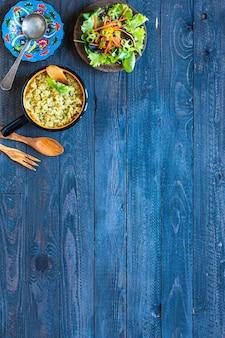 Risotto wegetariańskie z różnymi warzywami, na drewnianym stole rustykalnym.