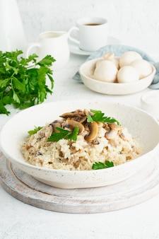 Risotto z pieczarkami na talerzu. kasza ryżowa z pieczarkami i natką pietruszki