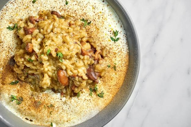 Risotto z przyprawami, sosem śmietanowym i kurkami w szarym talerzu na białym marmurze