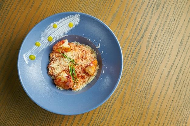Risotto z ryżem z krewetkami. ryż z owocami morza w niebieskim misce na drewnianej powierzchni. kuchnia włoska