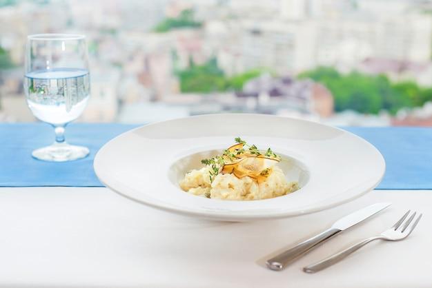 Risotto z serową gorgonzolą i gruszkami na białym talerzu na tle pejzażu miejskiego