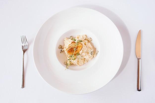 Risotto z serową gorgonzolą i gruszkami na białym talerzu