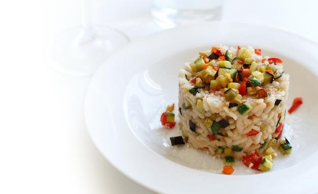 Risotto z warzywami na białej płytce z bliska włoskie jedzenie