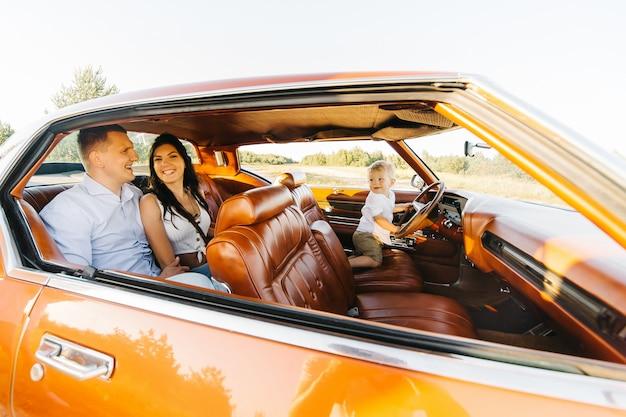 Riwiera w stylu retro. unikalny samochód. ładny blond chłopiec siedzi za kierownicą samochodu retro z rodziną. rodzice siedzą na tylnym siedzeniu.