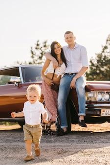 Riwiera w stylu retro. unikalny samochód. rodzice stoją w pobliżu samochodu w tle, syn gra uciekając przed nimi na pierwszym planie.
